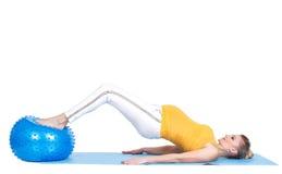 En gravid kvinna gör gymnastik med bollen Fotografering för Bildbyråer