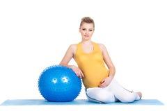 En gravid kvinna gör gymnastik med bollen Arkivbilder