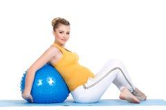 En gravid kvinna gör gymnastik med bollen Arkivbild