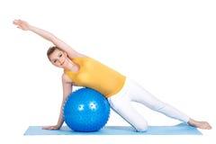 En gravid kvinna gör gymnastik med bollen Royaltyfri Foto