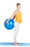 En gravid kvinna gör gymnastik med bollen Royaltyfri Fotografi