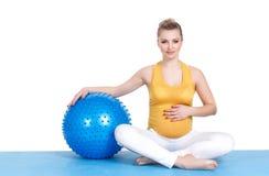 En gravid kvinna gör gymnastik med bollen Royaltyfria Bilder