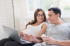 En gravid kvinna och en man ligger på sängen En kvinna rymmer en bärbar dator på hennes varv, en man rymmer en smartphone royaltyfria bilder