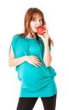 En gravid kvinna rymmer ett äpple arkivfoto