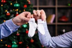 En gravid kvinna rymmer i henne sockor för handbarn` s, byten på bakgrunden av en julgran Iklätt en skjorta och skräp Arkivbild