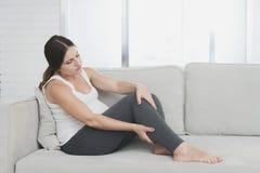 En gravid kvinna sitter hemma på en ljus soffa Henne benmen fotografering för bildbyråer