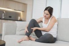 En gravid kvinna sitter hemma på en ljus soffa Henne benmen arkivbilder