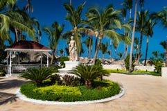 En grekiskt stilstaty och skydd lokaliseras bland palmträden arkivbild