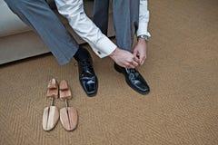 En groomsman binder upp hans nya skor bredvid ett par av skobårar arkivfoto