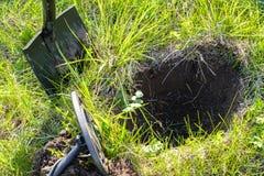 En grop grävde i sökande av skatten, en metalldetektor och en skyffel på en grön glänta royaltyfri bild