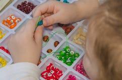 En gros plan de la main de bébé tisse, rassemble les perles et le bracelet de Images stock