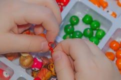 En gros plan de la main de bébé tisse, rassemble les perles et le bracelet de Photos libres de droits
