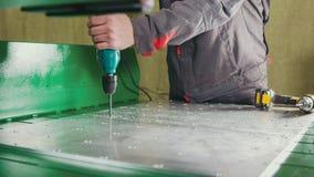 En gros plan du foret fonctionnant par les mains du ` s de travailleur et la plaque de métal de perçage photos stock