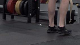 En gros plan - jeune bodybuilder fort faisant des postures accroupies avec des poids banque de vidéos
