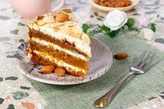 En gros plan le morceau de gâteau à la carotte végétarien avec des amandes sur une soucoupe et une fourchette près images stock