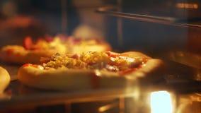 En gros plan, le processus de faire la mini pizza cuire au four de la pâte à levure dans un grand four industriel Pain de cuisson banque de vidéos