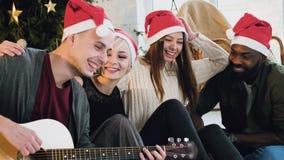 En gros plan une société jeunes et de beaux embrasse et joue une guitare sur le fond des décorations de Noël banque de vidéos
