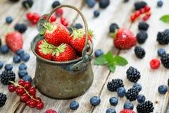 En grotesk hink på trätabellen som är full med bär - jordgubbar, vinbär, blåbär royaltyfri foto