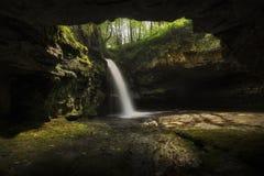 En grotta med en vattenfall arkivbilder