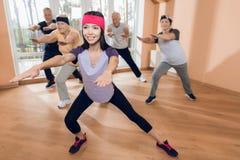 En grupp av äldre kvinnor och män som gör terapeutisk gymnastik i ett vårdhem Fotografering för Bildbyråer