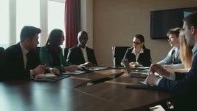 En grupp av affärsmän på tabellsamtalen lager videofilmer