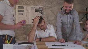 En grupp av anställda har gyckel som diskuterar teckningar, teamwork på kontoret stock video