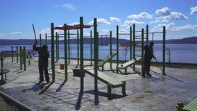 En grupp av arbetare förbereder lekplatsen för att täcka med rubber smula stock video