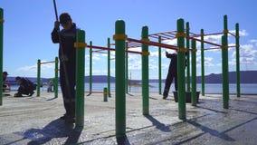 En grupp av arbetare förbereder lekplatsen för att täcka med rubber smula lager videofilmer