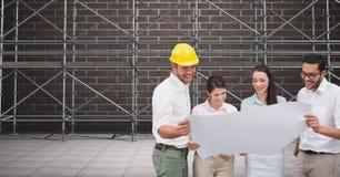 En grupp av arkitekter som framme ser en ritning av materialet till byggnadsställning 3D Arkivbilder