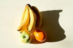 En grupp av bananer, ett äpple, en apelsin En mogen grupp av det knäpp gröna äpplet, mogen saftig apelsin arkivbild