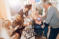 En grupp av barn och gamla människor i ett vårdhem gratulerar en äldre kvinna på hennes födelsedag royaltyfri foto