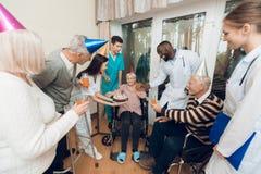 En grupp av barn och gamla människor i ett vårdhem gratulerar en äldre kvinna på hennes födelsedag arkivbilder