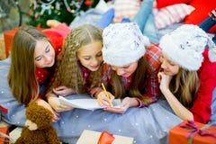 En grupp av barn som skrivar ett brev till Santa Claus Fotografering för Bildbyråer