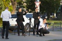 En grupp av bröllopfotografer på gatorna av Budapest rymmer en fotoperiod för ett par av nygifta personer Fotografering för Bildbyråer