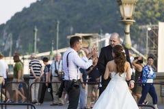 En grupp av bröllopfotografer på gatorna av Budapest rymmer en fotoperiod för ett par av nygifta personer Royaltyfri Foto