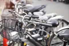 En grupp av cyklar som parkerar bredvid en väg i Japan Fotografering för Bildbyråer