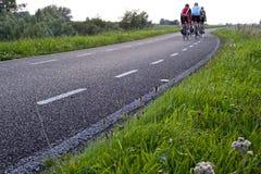 En grupp av cyklister som turnerar på en öde väg Arkivbild