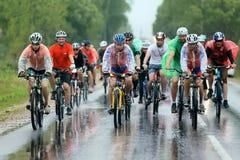 En grupp av cyklistracerbilen som springer i regnet Royaltyfri Foto