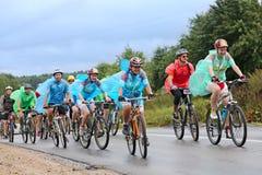 En grupp av cyklistracerbilen som springer i regnet Arkivbild