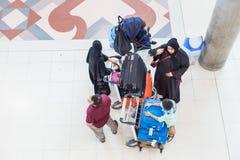 En grupp av den mellersta östliga familjväntan på flygplatsen med deras släpande royaltyfri bild