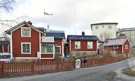 En grupp av det gamla röda trähuset med vitklippning som är höger i mitten av Vaxholm med nyare byggnader bakom Royaltyfri Foto