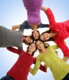 En grupp av det lyckliga tonåringinnehav räcker tillsammans Arkivbild