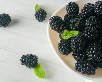 En grupp av dewberries på en vit platta Ljus bakgrund En hög tangent arkivfoto