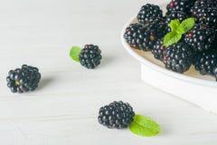 En grupp av dewberries på en vit platta Ljus bakgrund En hög tangent fotografering för bildbyråer