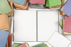 En grupp av färgrika böcker med mellanrum ett öppnade i mitt royaltyfria bilder