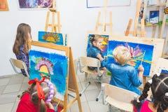 En grupp av förskole- studenter och den unga läraren i målarfärg för teckningsgrupp i gouache skolflickaafroamerican för blandat  arkivbilder