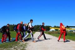 En grupp av fallskärmshoppare går på en nivå för ett hopp royaltyfria bilder