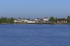 En grupp av gamla och nya hus som förbiser floden Arkivfoton