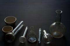 En grupp av gamla smutsiga kemiska glasflaskor och provrör på svart bakgrund med kopieringsutrymme för din text royaltyfria foton