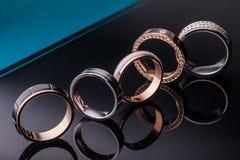 En grupp av härliga förlovningsringar med diamanter på ett trendigt mörker - blå bakgrund med reflexion Closeup guld, silver, pl Royaltyfria Bilder
